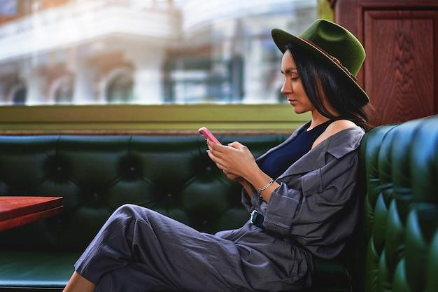 Стильная женщина-путешественница в фетровой шляпе с помощью телефона в кафе-магазине