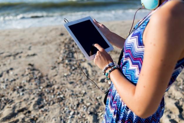 タブレットを使用して、熱帯のビーチの上を歩くスタイリッシュな女性