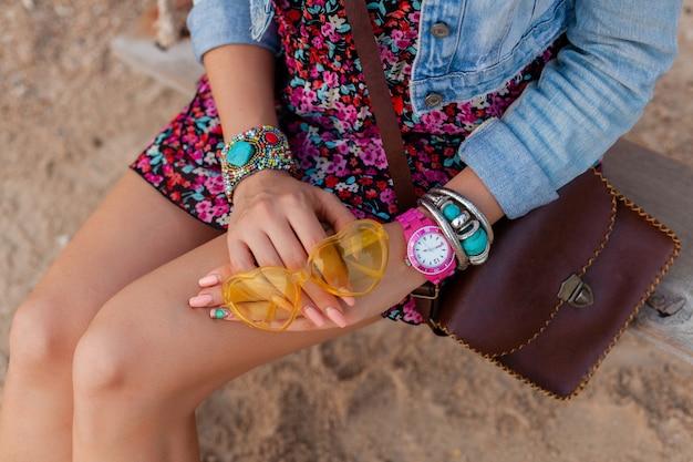 Donna alla moda in vacanza su beachhands con gioielli e borsa accessori colorati gialli sunglasess