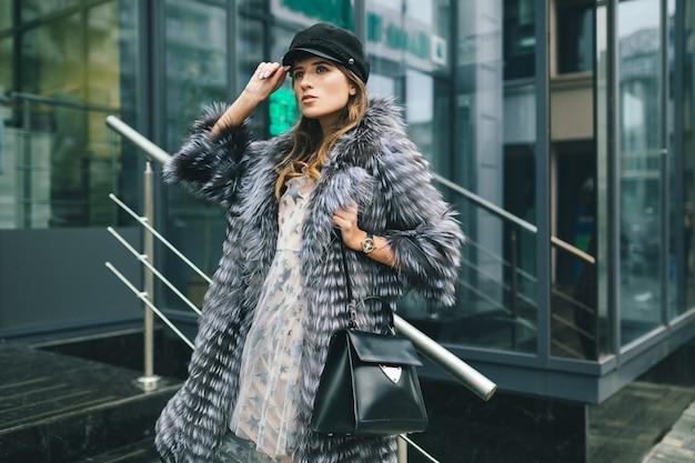 Stylish woman walking in city in warm fur coat, winter season, cold weather, wearing black cap, holding leather bag, street fashion trend, urban look