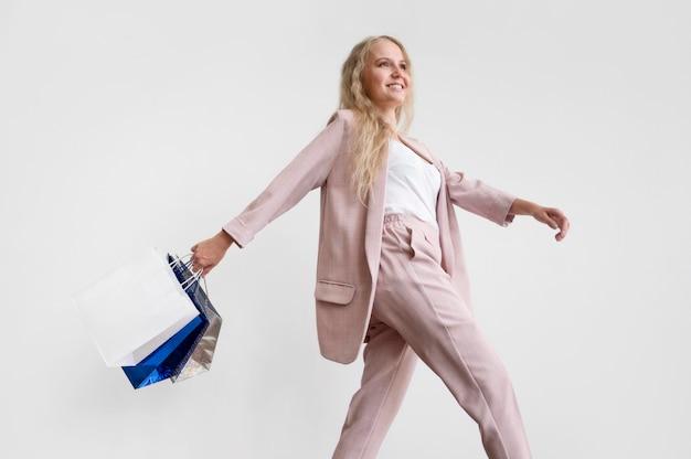 買い物袋と一緒に歩いているスタイリッシュな女性