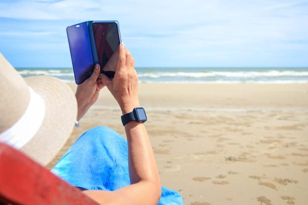 Стильная женщина в синем длинном платье. посидите на солнышке на берегу моря, любуясь красивыми природными пейзажами. туристический морской пляж таиланд, азия, летние каникулы, каникулы, путешествия