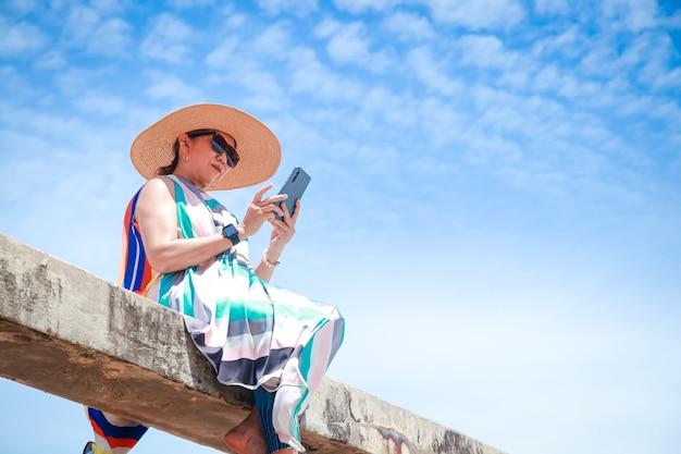 Стильная женщина в ярком длинном платье и держит смартфон, чтобы фотографировать.