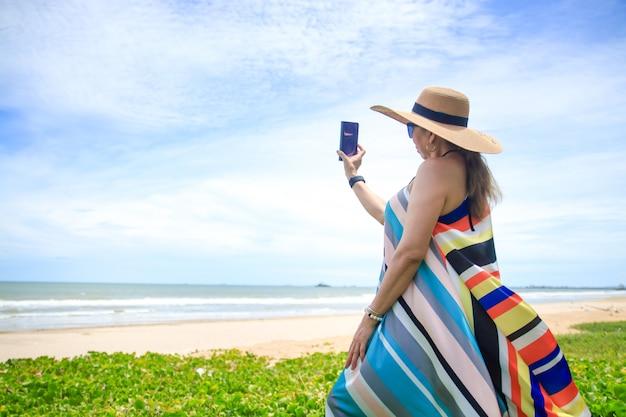 Стильная женщина в ярком длинном платье. встаньте на солнышке на берегу моря, глядя на красивые природные пейзажи. туристический морской пляж таиланд, азия, летние каникулы путешествия путешествие.