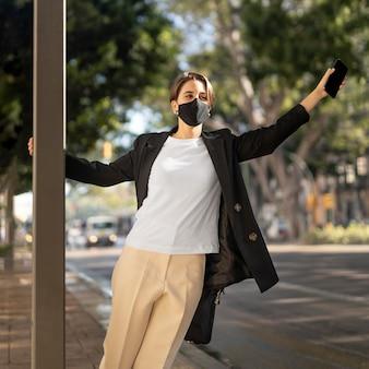 外で医療マスクを身に着けているスタイリッシュな女性