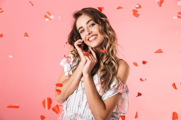ピンクで隔離の落ちてくる紙吹雪の下に笑顔で立っているドレスを着ているスタイリッシュな女性