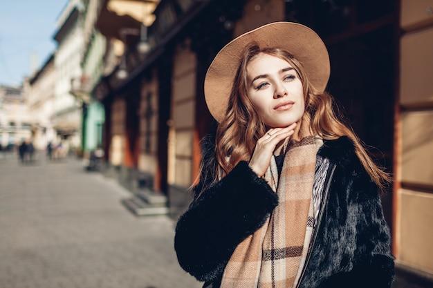 毛皮のコート、ベージュの帽子、スカーフを着てスタイリッシュな女性