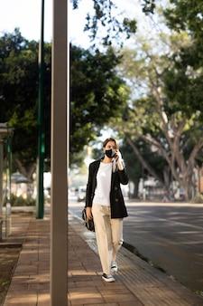 Donna alla moda che indossa una mascherina medica all'esterno e parla al telefono