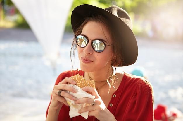 赤いブラウスと大きな帽子を身に着けているスタイリッシュな女性