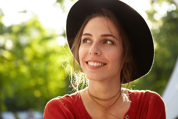 Stylish woman wearing red blouse and big hat