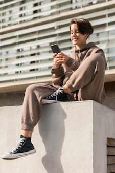 Elegante donna che indossa abbigliamento sportivo e controlla il suo telefono