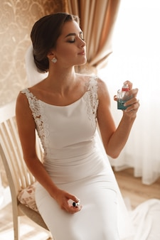 Stylish woman wearing a white dress spray tender perfume