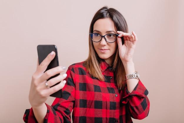 スタイリッシュな女性は、孤立した壁に幸せな感情とスマートフォンで自分撮りを作る眼鏡をかけています。孤立した壁、テキストの場所に真の感情を持つガジェットを使用して若い女性