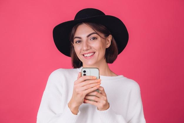 Donna alla moda in maglione casual bianco e cappello sulla parete rosa rossa