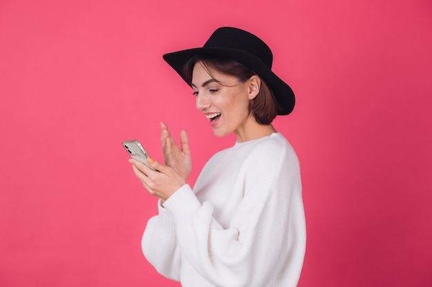 Stylish woman in white casual sweater and hat on red pink wall