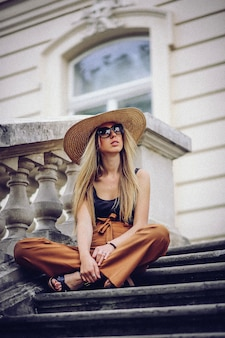 Stylish woman in white hat sitting on stairs