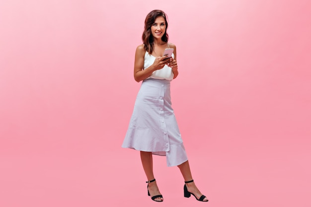 Stylish woman in white outfit looking at camera and holding smartphone. smiling lady in light blue long skirt and top posing on pink background.