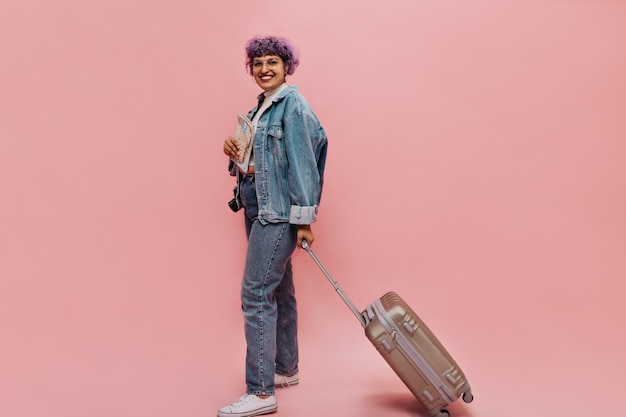Stylish woman in wide denim jacket holds suitcase and plane tickets. l