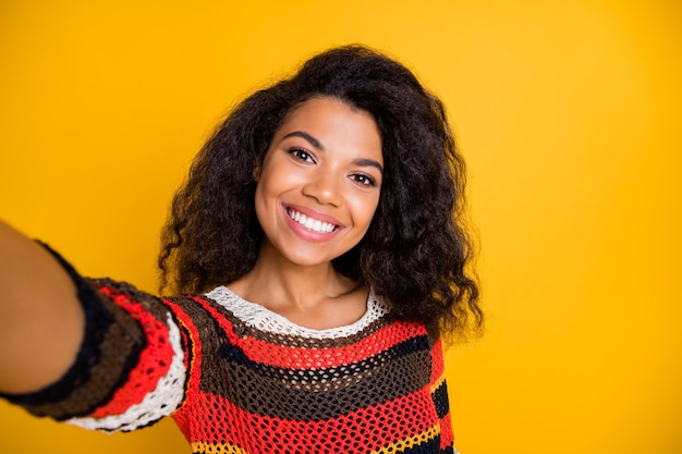 Stylish woman with afro hairstyle posing against the orange wall