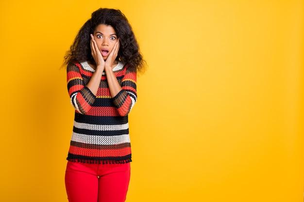 Стильная женщина с афро-прической позирует на оранжевой стене