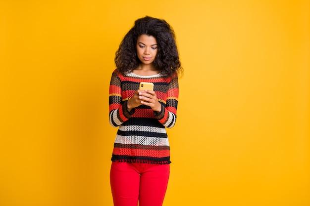 オレンジ色の壁にポーズをとってアフロの髪型を持つスタイリッシュな女性