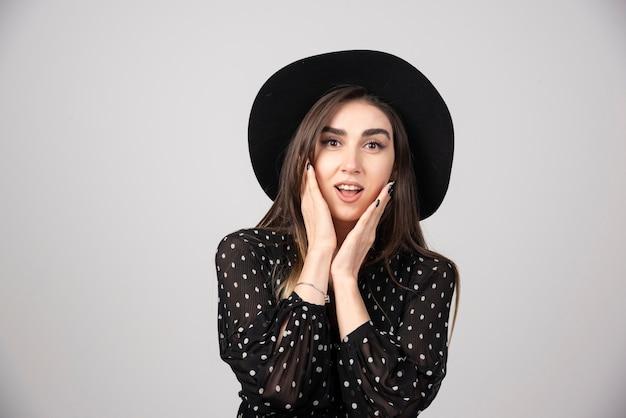Donna alla moda con cappello nero che guarda l'obbiettivo.