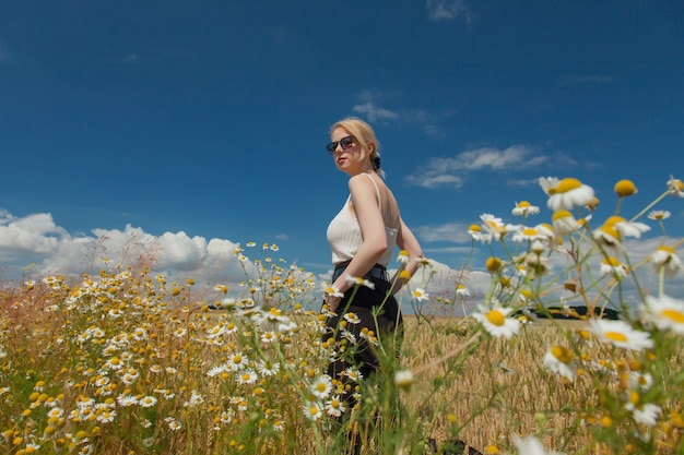 Stylish woman with blond hair posing in formal clothes on chamomile meadow