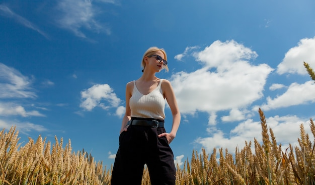 Stylish woman with blond hair posing in formal clothes in wheat field