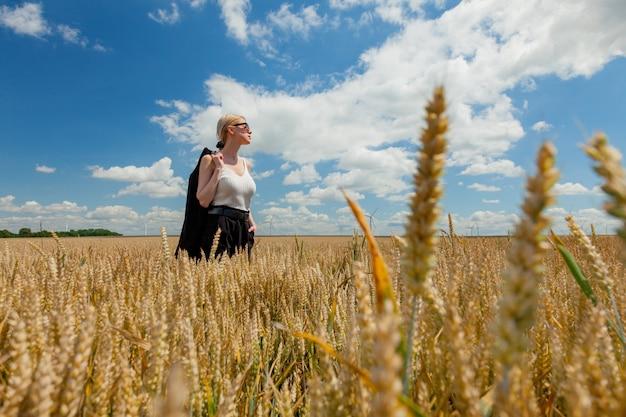 Стильная женщина со светлыми волосами позирует в формальной одежде на пшеничном поле
