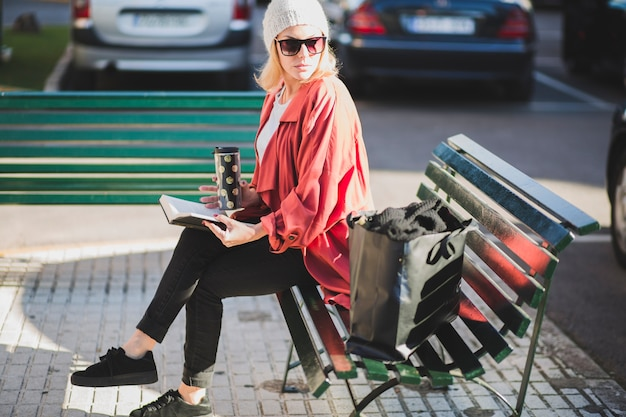Stylish woman with book and cup