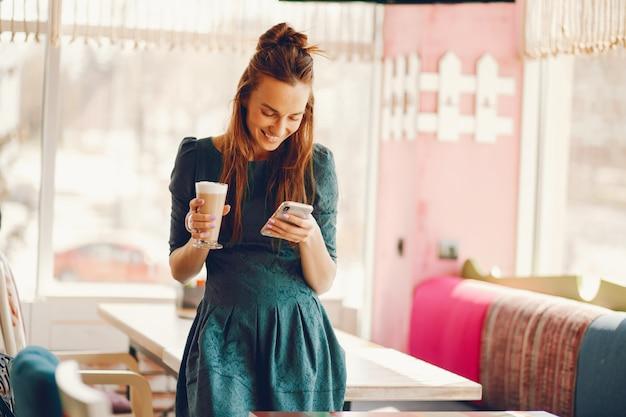 スタイリッシュな女性は長い髪と緑のドレスでテーブルにカフェに立っている