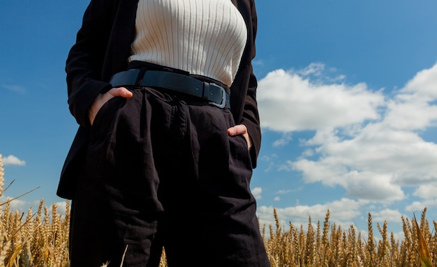 Stylish woman with posing in formal clothes in wheat field. torso view