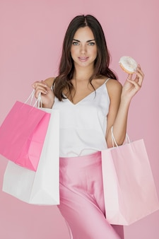 買い物袋とドーナツを持つスタイリッシュな女性