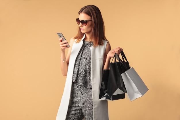 ショッピングバッグを持つスタイリッシュな女性は、ベージュの背景に分離されたスマートフォンを使用します