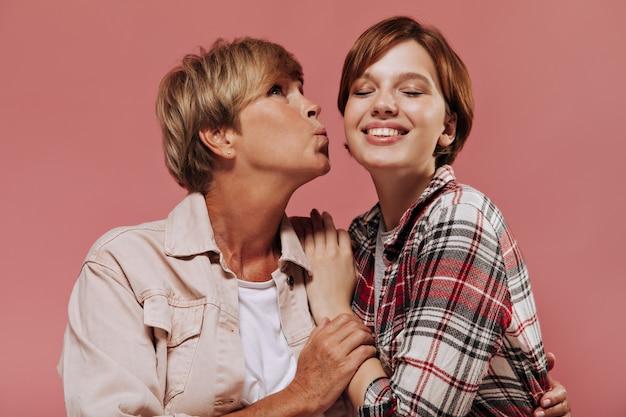 ピンクの背景に格子縞の衣装で頬の笑顔の女の子にキスするベージュの服を着た短いブロンドの髪型のスタイリッシュな女性。