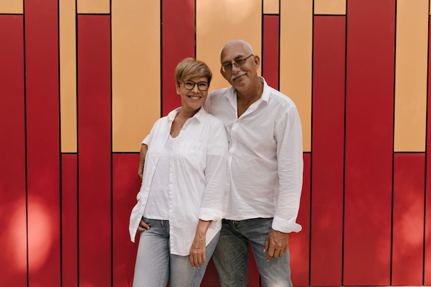 Stylish woman with short hair in eyeglsses and light blouse smiling and hugging with old man in white shirt and jeans on red and orange.