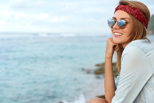 Stylish woman with sunglasses sitting on the beach