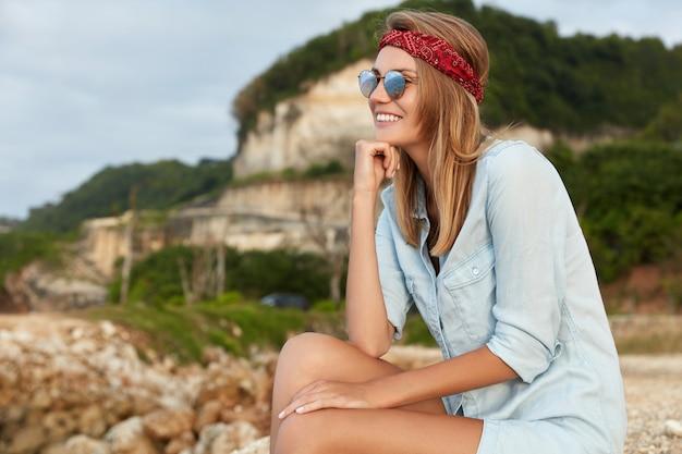ビーチに座っているサングラスを持つスタイリッシュな女性