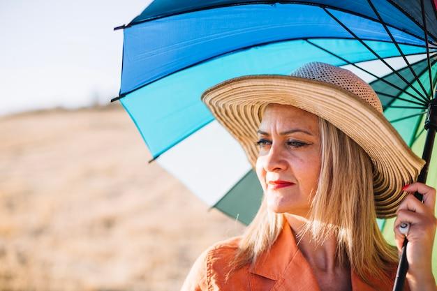 Elegante donna con ombrello sulla natura
