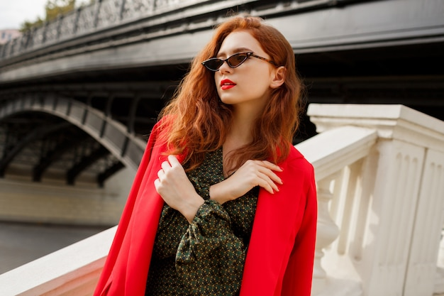 Stylish woman with wavy ginger hairs posing outdoor in red jacket.
