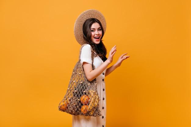 Donna alla moda con capelli ondulati posa con borsa eco con frutta. ragazza in cappello di paglia sorride su sfondo arancione.