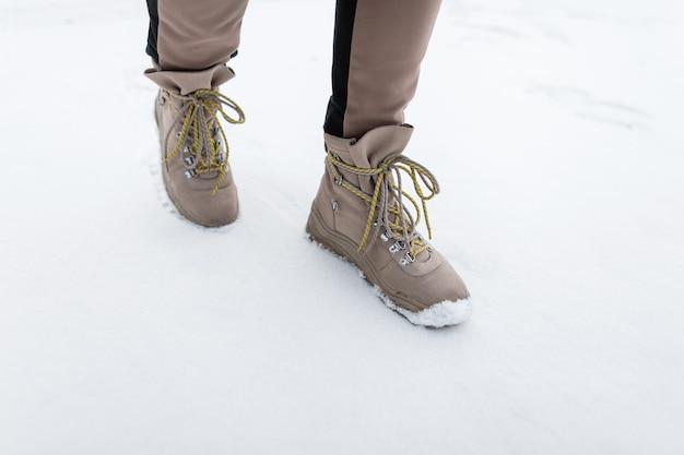 노란색 끈 겨울 가죽 부츠와 세련 된 여자. 소녀는 세련된 따뜻한 겨울 신발을 착용합니다. 확대.