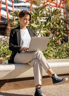 Stylish woman working on laptop outdoors