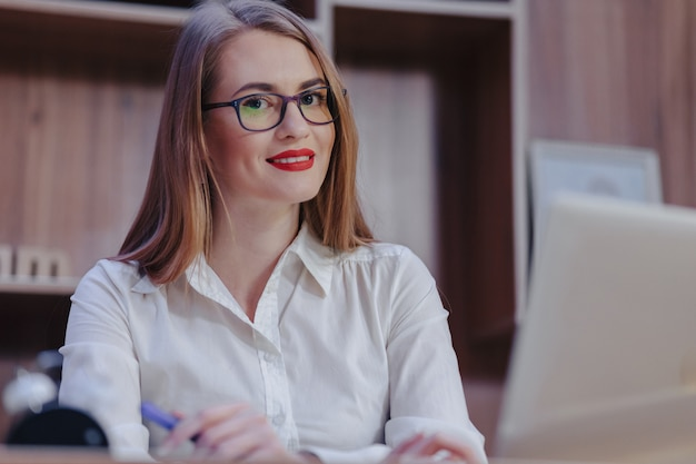 Stylish woman works at a laptop desk in a modern office