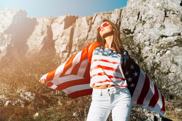 Stylish woman wrapped in american flag in nature