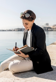Stylish woman writing in a notebook