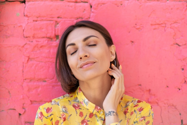 Stylish woman in yellow summer dress on pink brick wall happy calm and positive