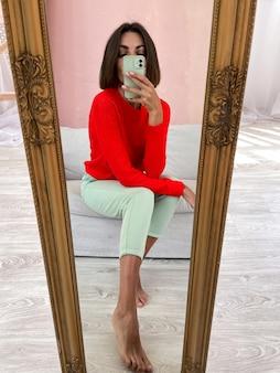밝은 빨간색 스웨터와 민트 그린 바지를 입은 집에서 세련된 여성이 전화로 거울에 사진 셀카를 찍습니다.