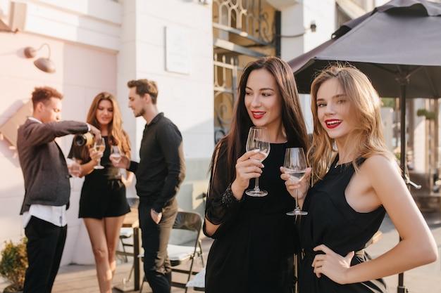 Стильные женщины что-то обсуждают, пьют шампанское на улице