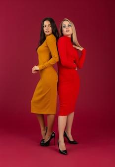 Стильные женщины в желтом и красном вязаном платье осенне-зимней моды позируют изолированно на красной стене